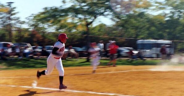 Softball player running down the baseline after a hit.